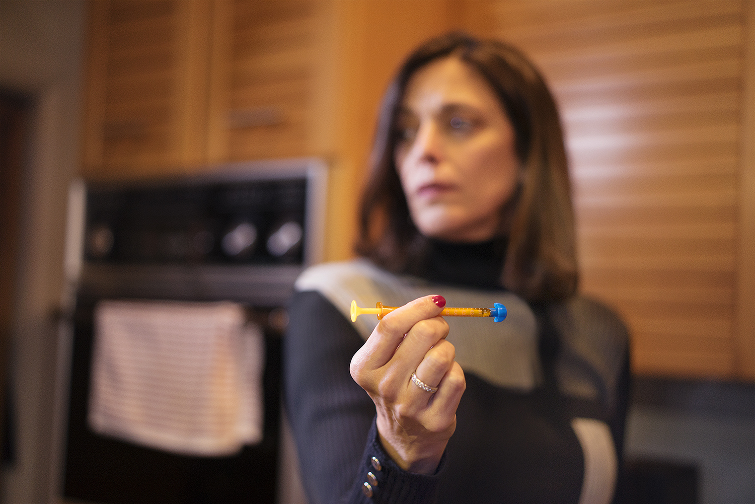 Beth Collins holding an oral syringe to dispense medical marijuana